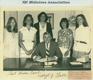 Governor Hugh Gallen signing  New Hampshire midwifery legislation, with group of women including Carol Leonard looking on, 15 August 1981