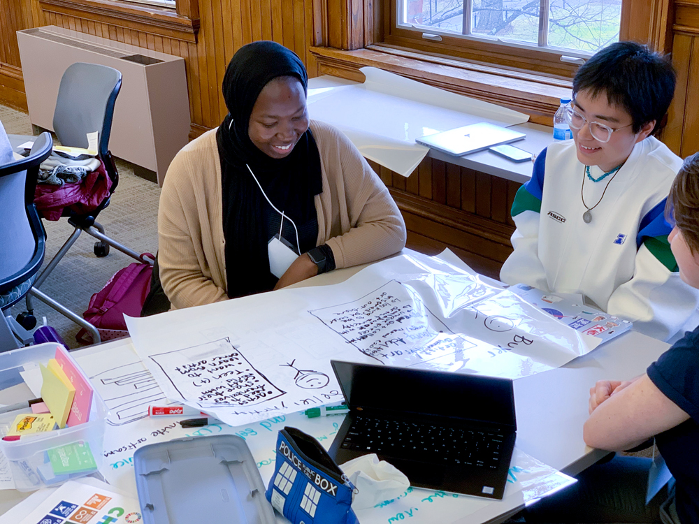 Three students working in a small group. The main figure is a young black woman in a headscarf.