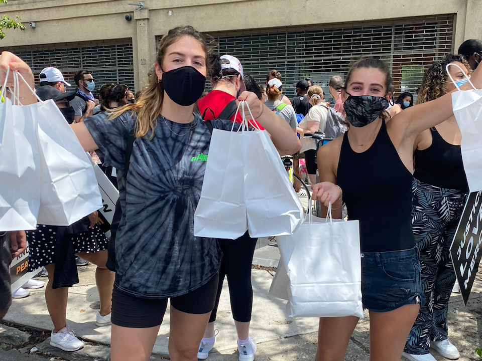 Two white friends wearing masks hold up bags of food