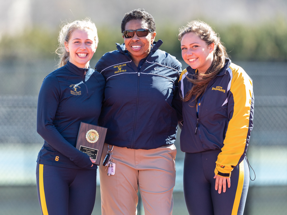 A coach with two track and field athletes, all smiling into the camera