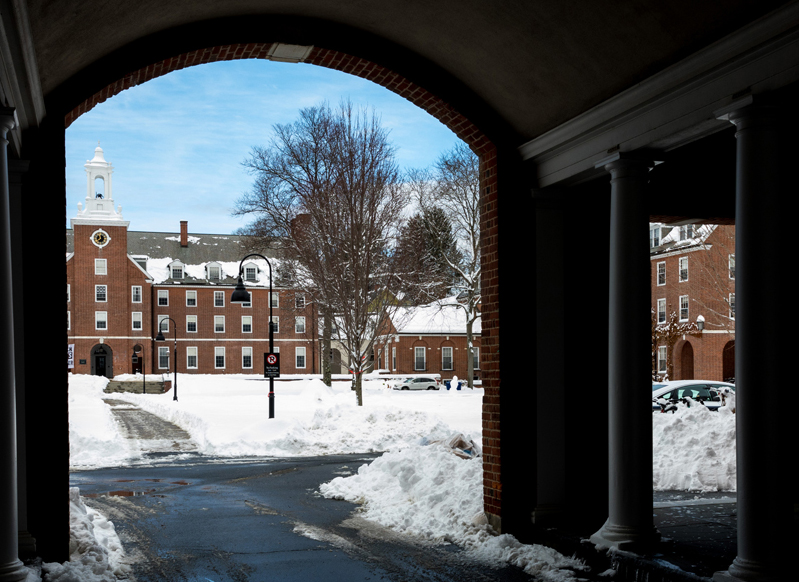winter courtyard and blue sky seen through an archway