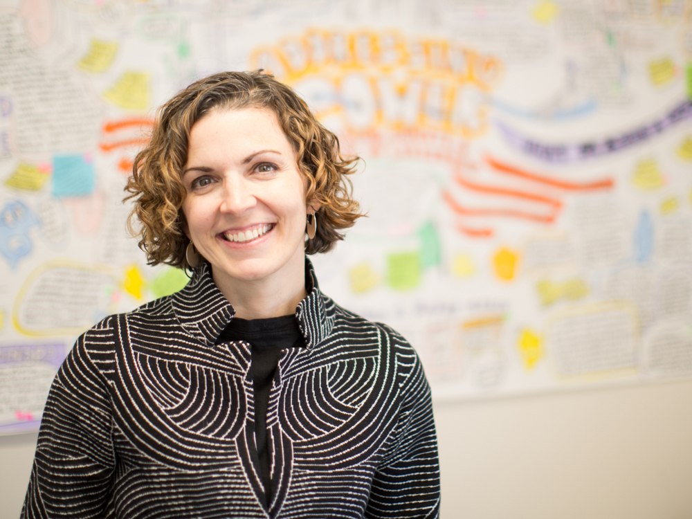 Erin Cohn against a out-of-focus white board covered with writing in bright marker