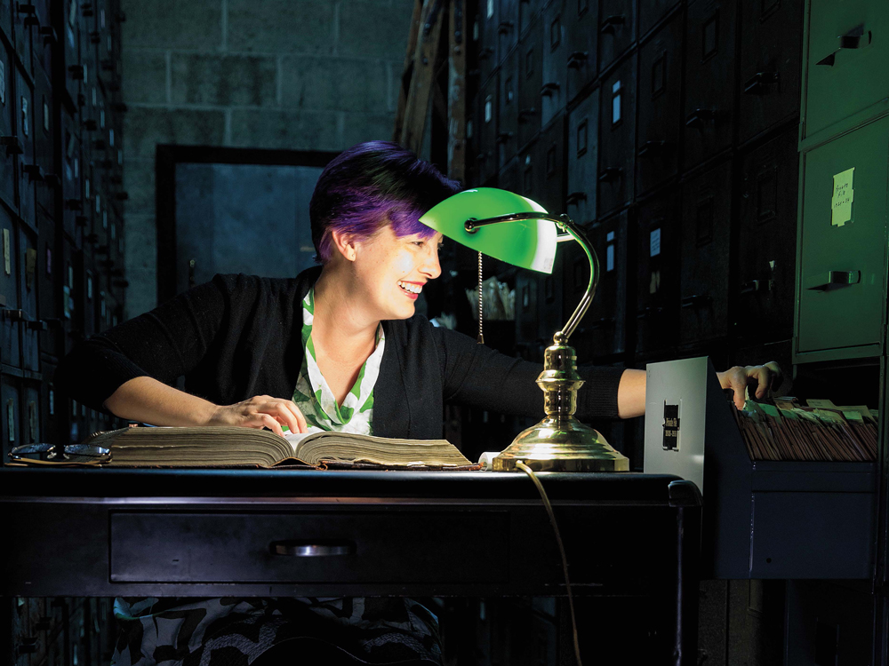 Kory Behny Stamper smiling while looking in a filing cabinet while seated under a green table lamp.