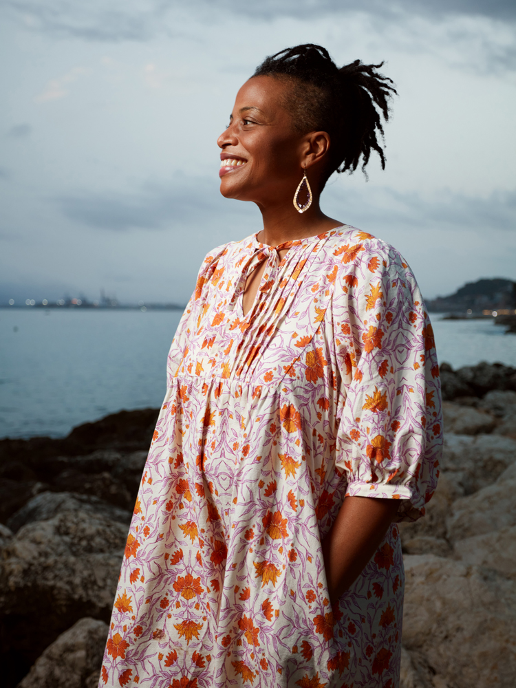 Lori Tharps '94, smiling, on the beach in Málaga in southern Spain in a white dress with orange flowers