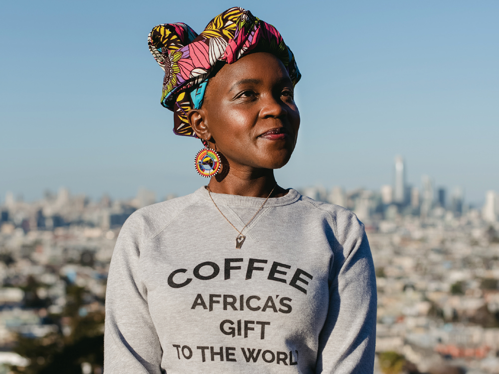 "Margaret Nyamumbo wearing a sweatshirt with the slogan ""Coffee: Africa's Gift to the World"""