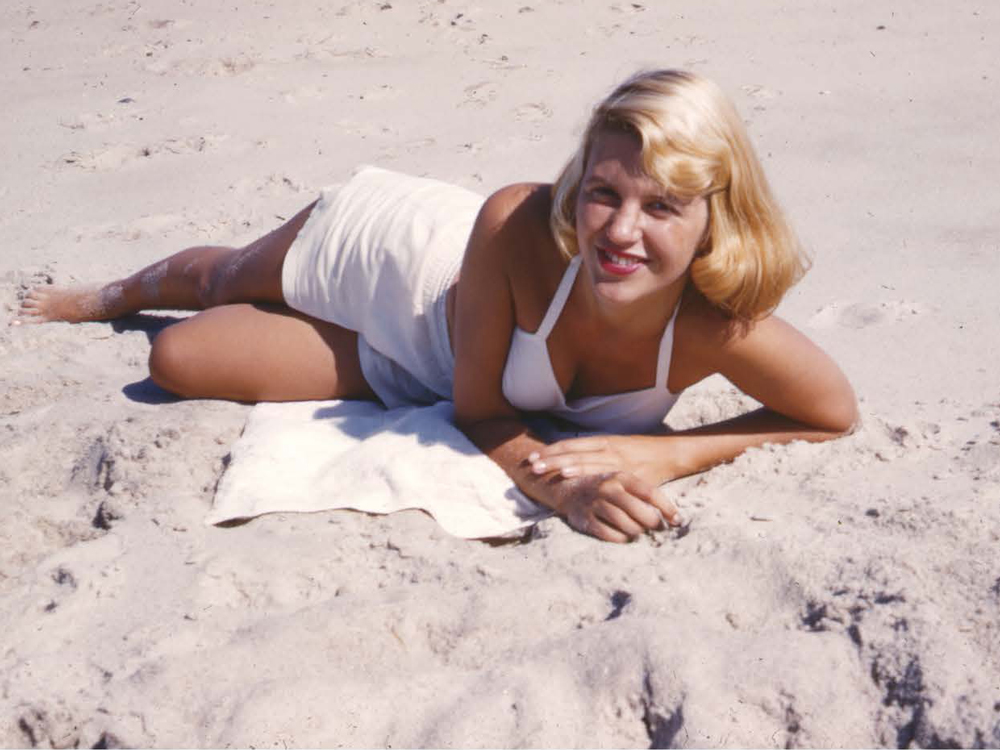 Sylvia Plath in a white bathing suit posing on the beach, smiling at the camera
