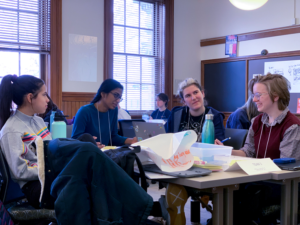 Group of four students, including people of color and a gender non-conforming student, doing group work