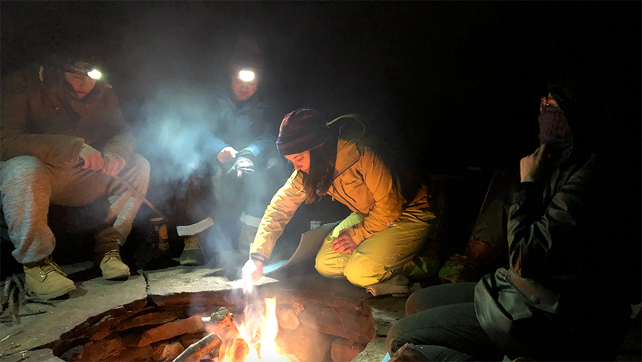 Students cook outdoors on backpacking stoves.