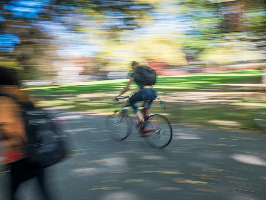 Motion-blurred photo of a student riding a bike on campus