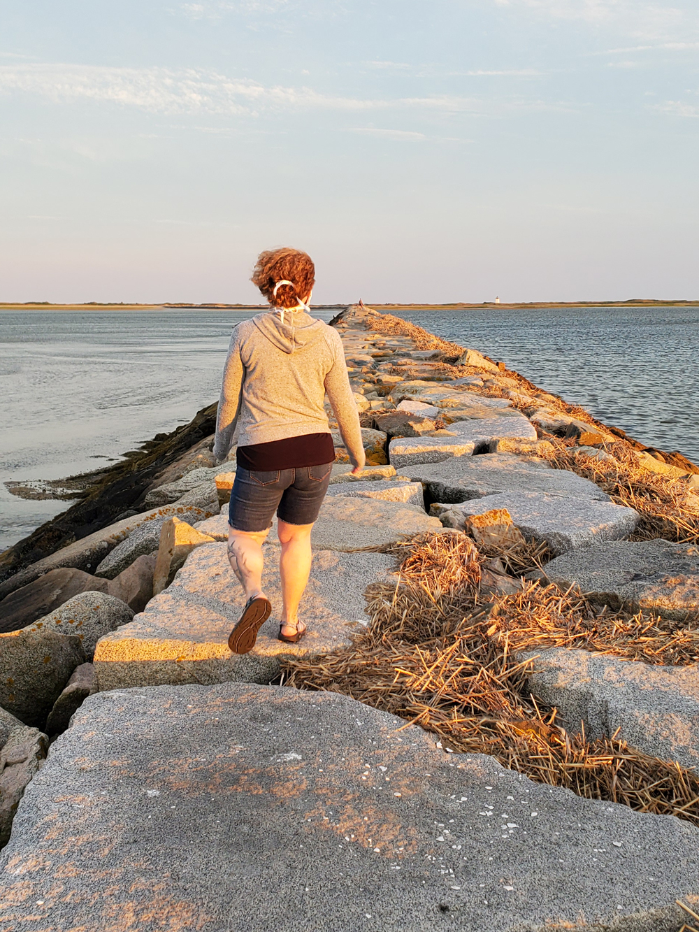 Person walking the causeway with mask strings in her curly hair