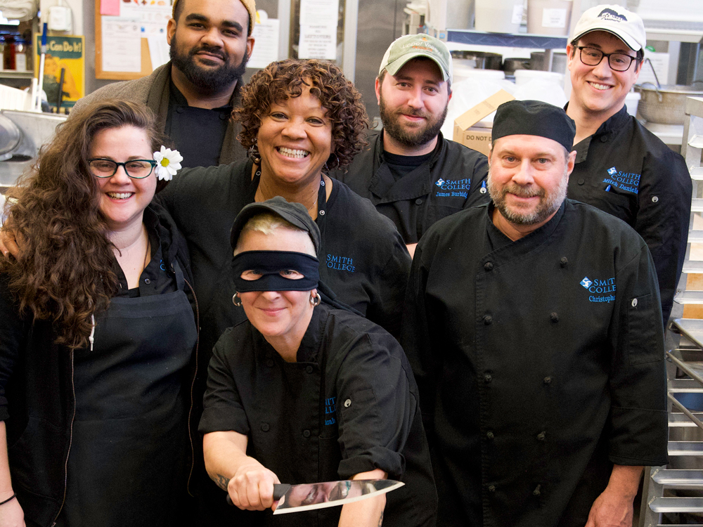 Group of dining services staff smiling at the camera. One is holding a cooking knife in mock battle.