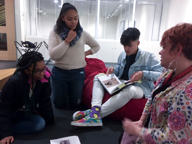 Three students of color looking at a copy of the exhibit book Black Refractions while an art educator looks on.
