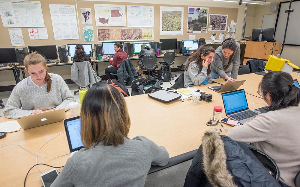 Multiple students work with laptops on a shared table while other students work on a row of desktop computers