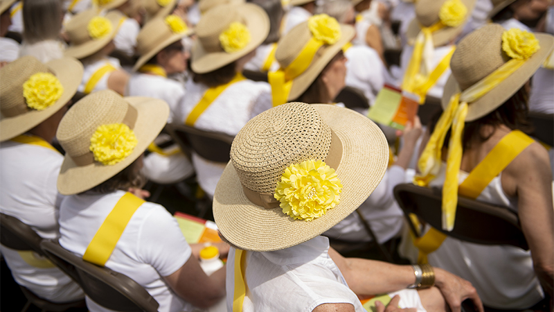 Alumnae wearing matching hats sitting at Ivy Day