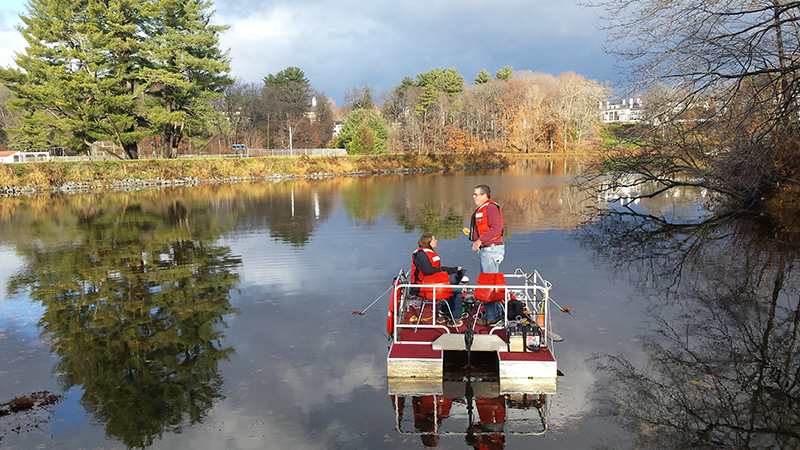 Student and professor conducting research on the pond
