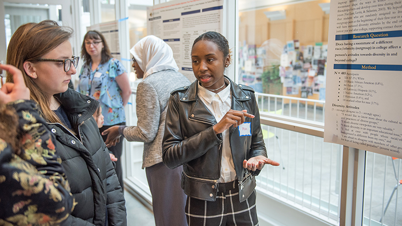 Student discussing her poster in the campus center
