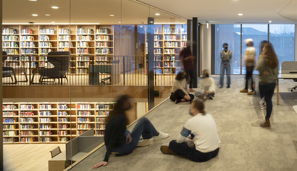 Students sitting on the ground, talking, overlooking another level of the library