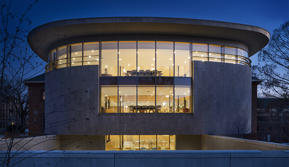 Outside view of the side Neilson library at night, with windows illuminated inside