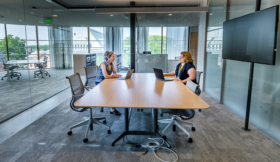 Two people sitting at a table in a collaborative room in Neilson