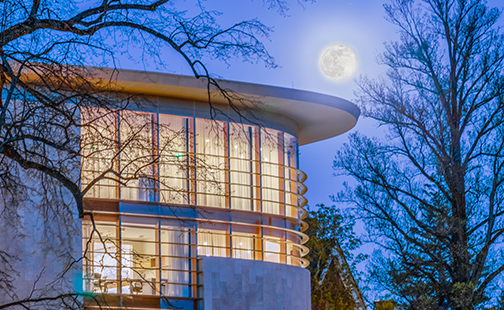 Neilson Library exterior jewel box will full moon behind it