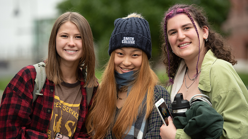 fall campus group scene of three students outside smiling