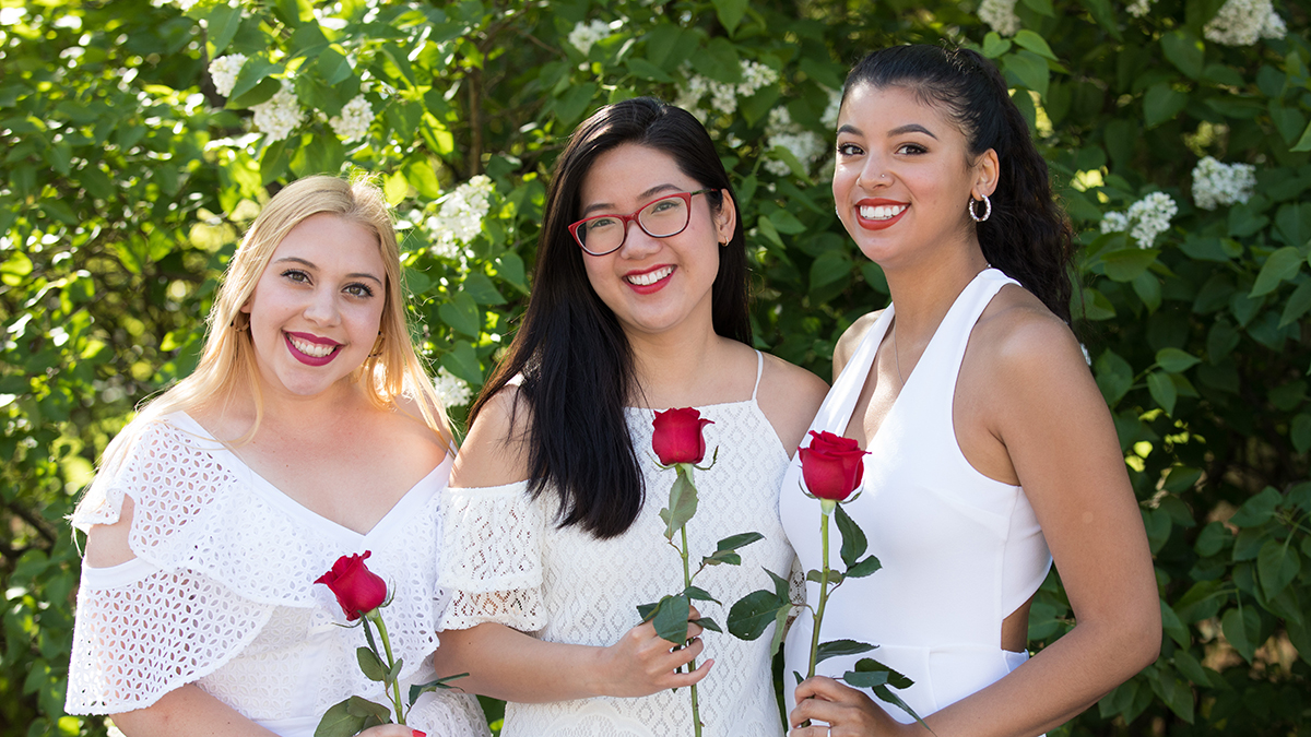 Three students holding red roses on Ivy Day