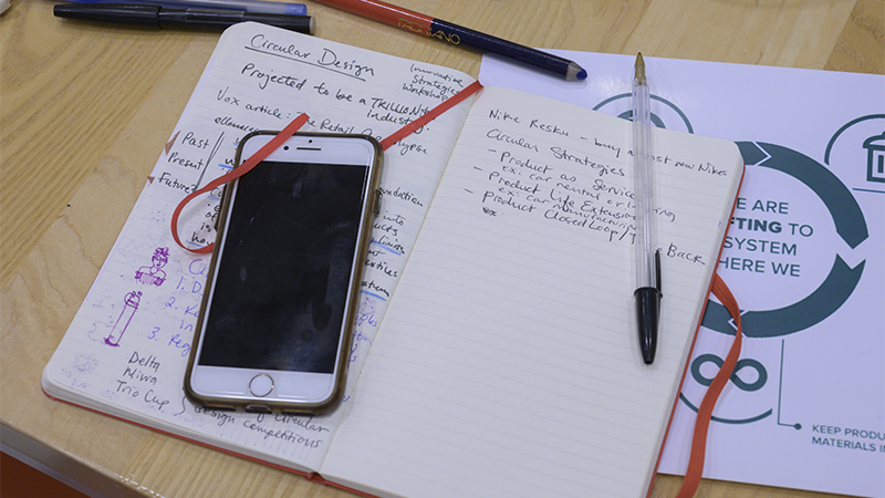 An iPhone, a notebook, and pens spread out on a desk
