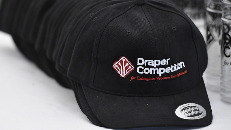 A stack of hats featuring the Draper Competition logo