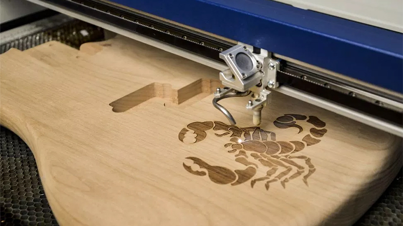 Lasercutter engraving a scorpion design into wood