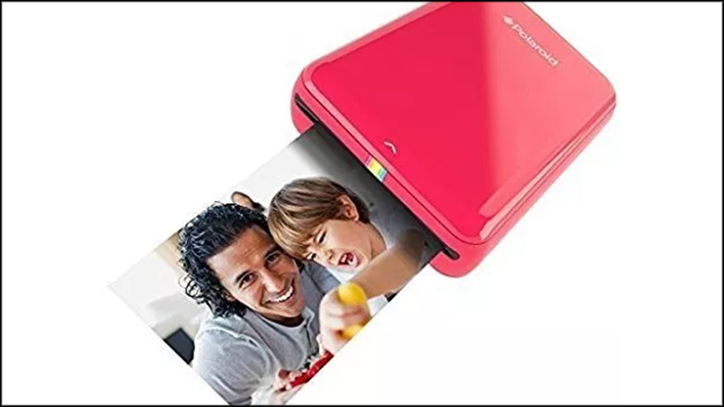 Photo of a red Polaroid Zip Photo Printer printing a photo