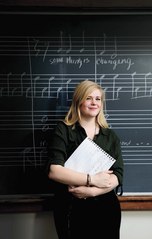 Liberal Arts - Music - A woman stands in front of a blackboard covered in musical notation.