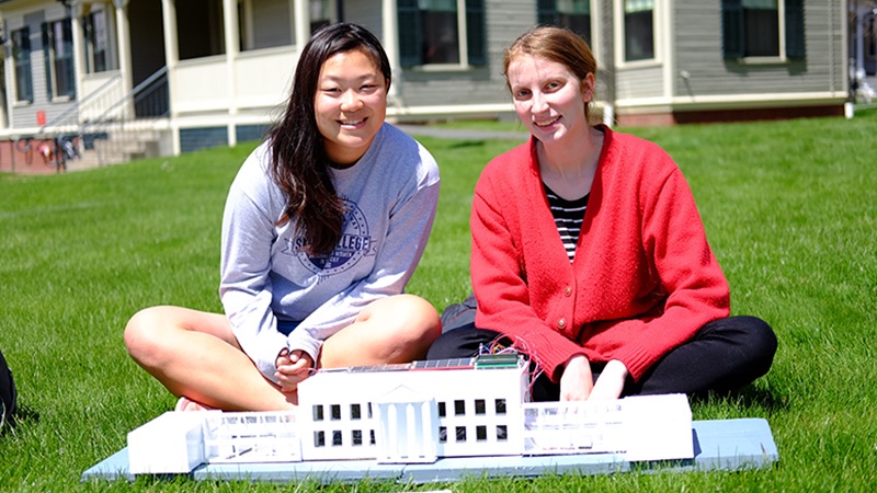 Two students outside with a model house they built