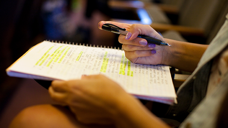 Close-up of a student taking notes in class