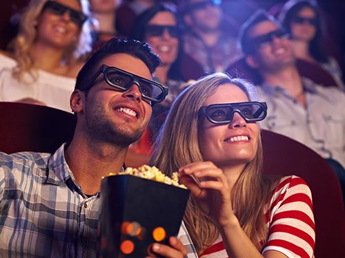 Couple wearing 3D glasses and sharing popcorn