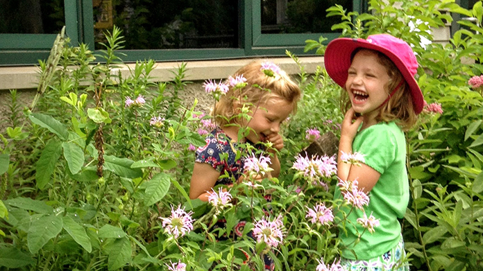 Two girls looking at flowers outside
