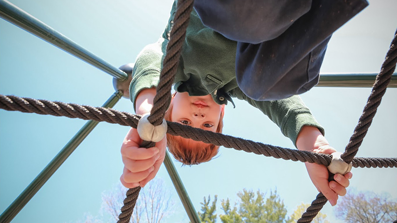 child upside down on jungle gym