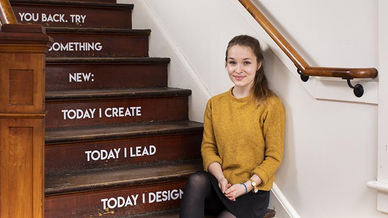 Madeline Turner sitting on the steps in Design Thinking room