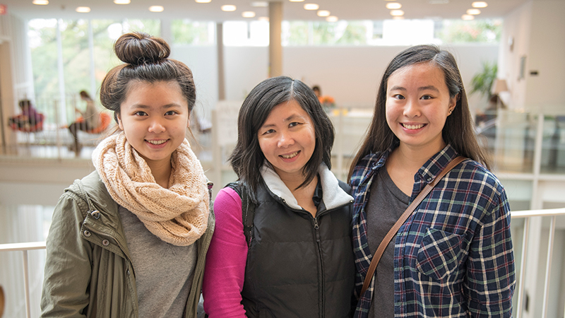 Two students with their mother in the campus center