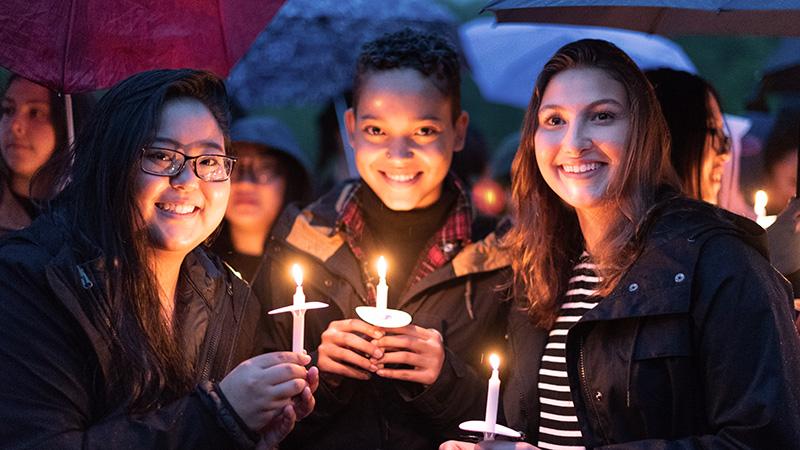 Three students holding candles on Illumination Night