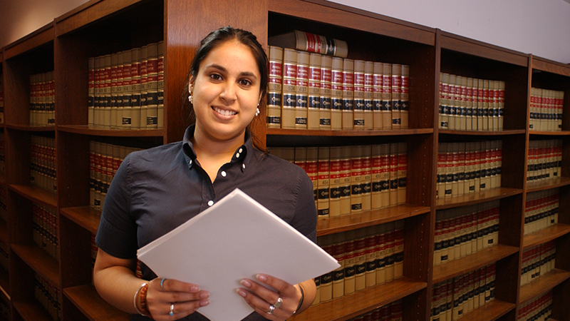 Woman standing in a law library in front of shelves of books