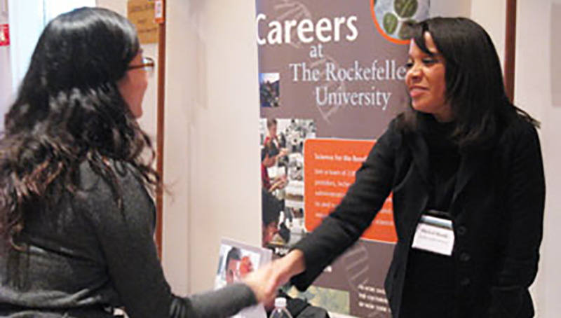 Two women shaking hands at a job fair