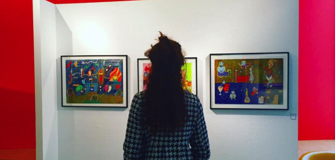 Woman looking at works on art on gallery wall of Nolen Art Lounge, Smith College
