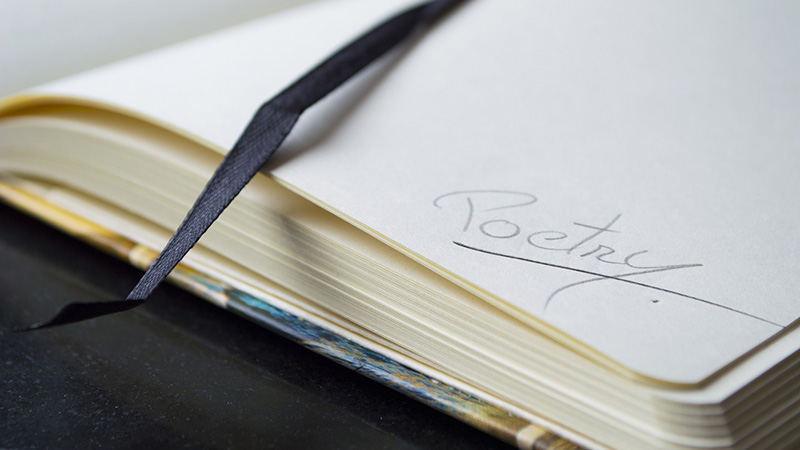 "Photo of journal with the written word ""poetry"""
