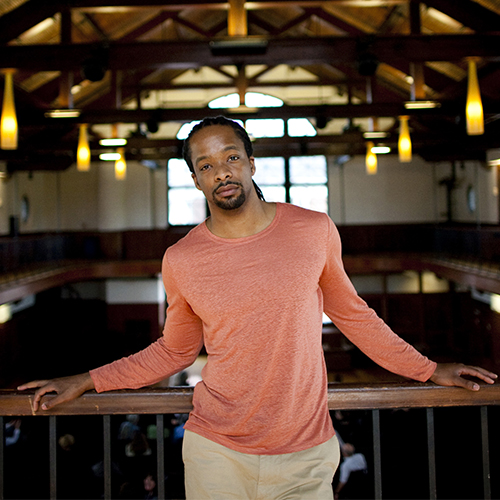 Jericho Brown leans on a wooden beam, looking directly into the camera. Photo credit: Stephanie Mitchell