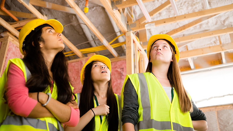 Students in construction helmets learn about green building