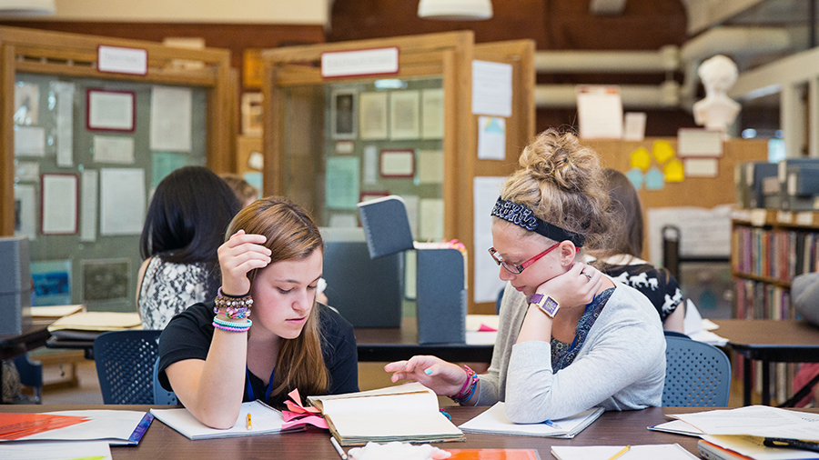 Two young women looking at Smith Archives during precollege summer history program