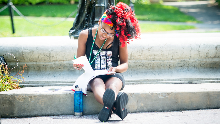 Young woman writes in journal near Smith College fountain during women's writing summer program