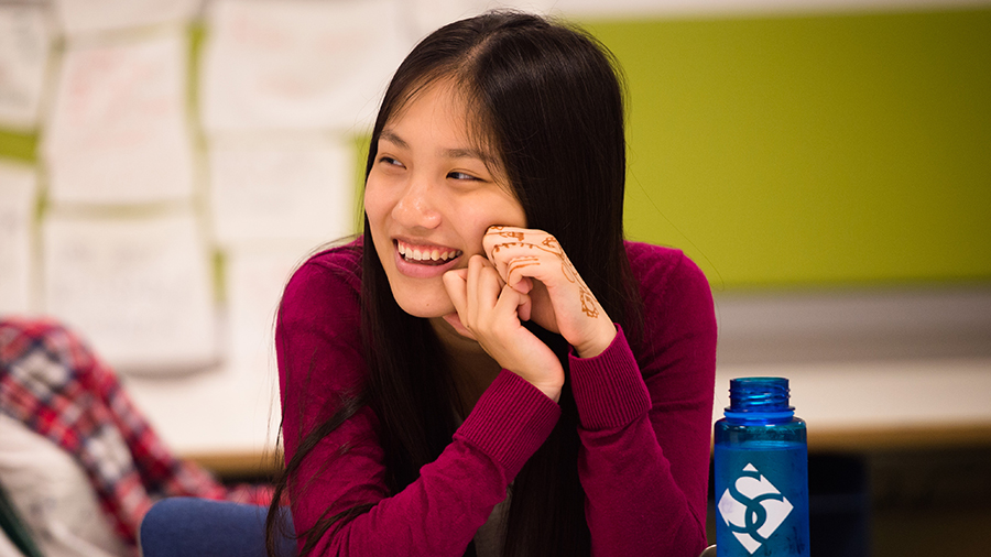 Young woman laughs in classroom, Smith College