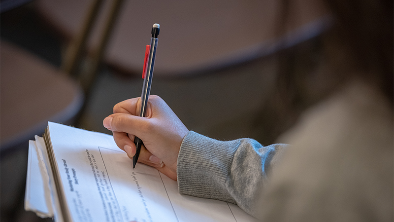 Image of student writing with pen in hand