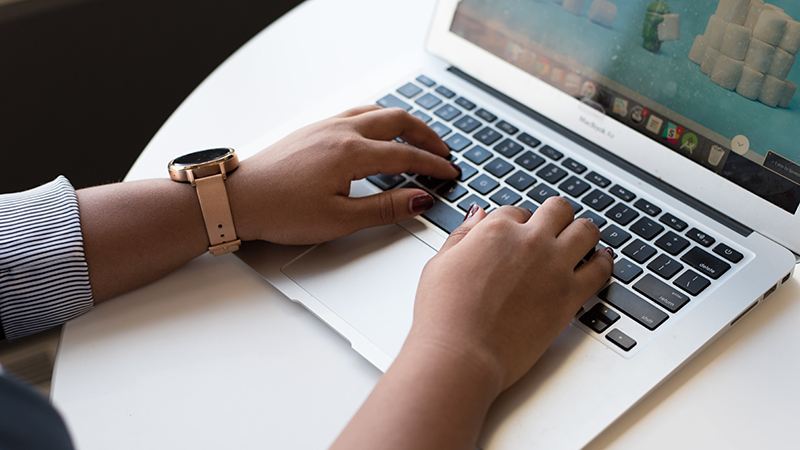 Image of a woman's fingers typing on a computer keyboard